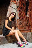 Glamour lady in black sitting on old staircase. — Stock Photo