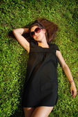 Charming lady in black dress lying on grass. — Stock Photo