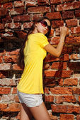 Charming lady in yellow dress next to old wall. — Stock Photo