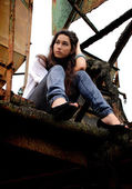 Beautiful girl sitting in an old factory. — Foto de Stock