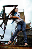Beautiful girl stanging in an old factory. — Stock Photo