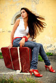 Charming model sitting on red suitcase. — Stock Photo