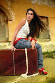 Beautiful model sitting on red suitcase. — Stock Photo
