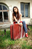 Bored girl with red suitcase. — Stock Photo