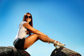Fashion model in high hill shoes an a stone. — Stock Photo