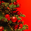 Stock Photo: Part of Christmas tree on red background.