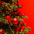 Part of Christmas tree on red background. — Stock Photo