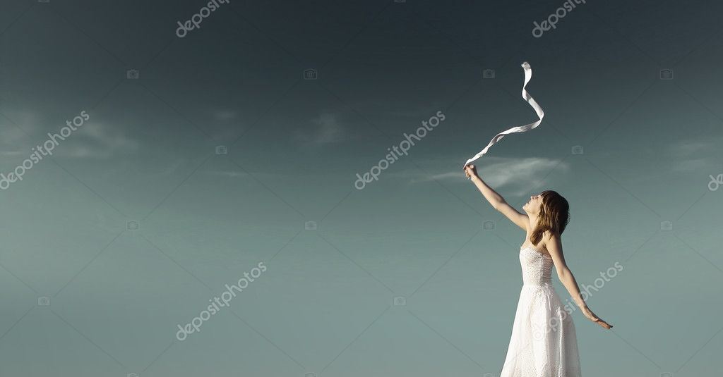 Young woman in white dress with white ribbon over dark sky background  Stock Photo #3271440