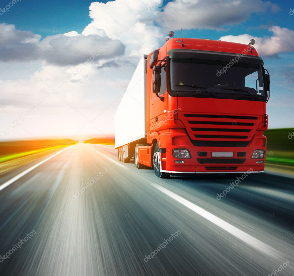 Red truck on blurry asphalt road over blue cloudy sky background — Stok fotoğraf #3271446