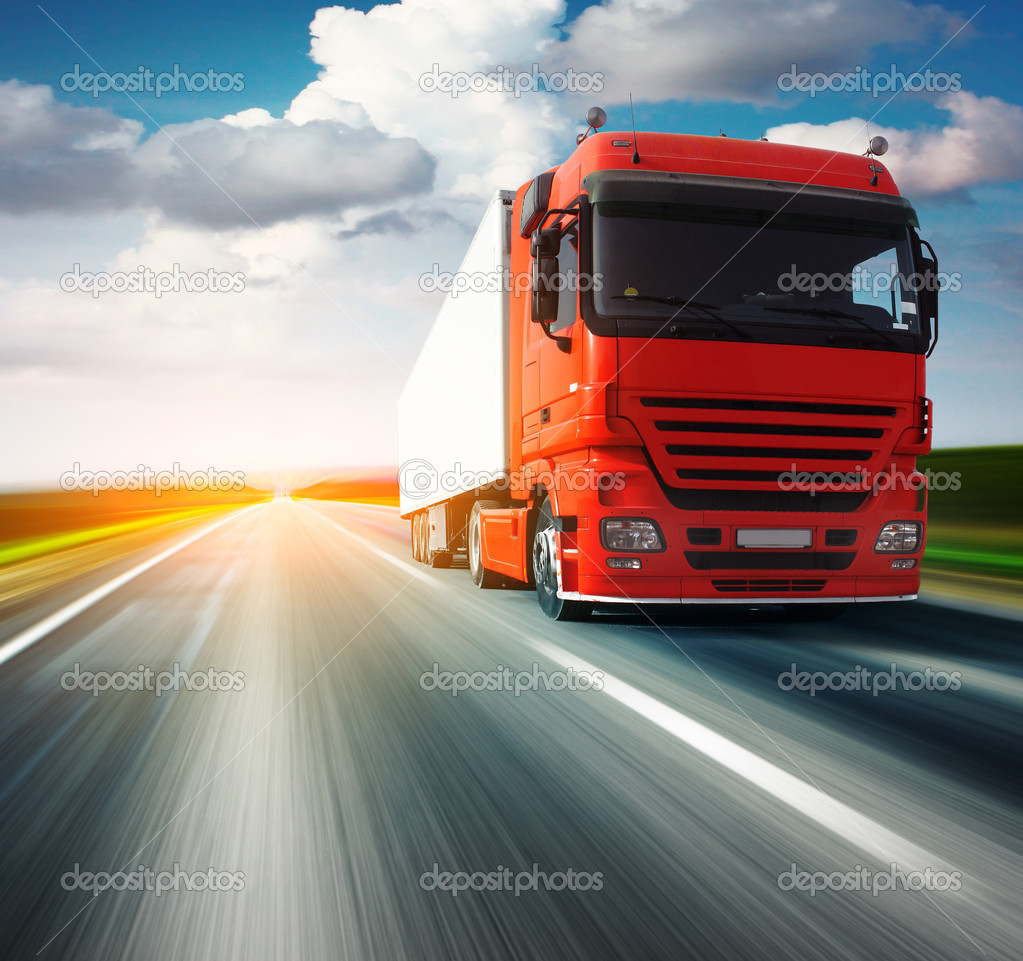 Red truck on blurry asphalt road over blue cloudy sky background — Stock fotografie #3271446