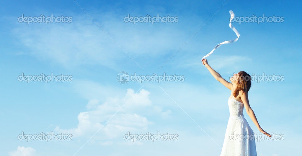 Young woman in white dress with white ribbon over blue cloudy sky background — Stock Photo #3271519
