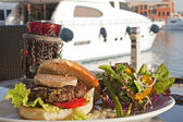 Gourmet beef burger with motor yacht — Stock Photo