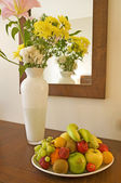 Vase of flowers and a bowl of fruit — Stock Photo
