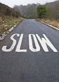 Slow sign on a country lane — Stock Photo