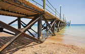 Wooden jetty on a tropical beach — Stock Photo