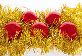 Red christmas balls on gold tinsel — Stock Photo