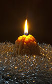 Christmas candle in silver tinsel — Stock Photo