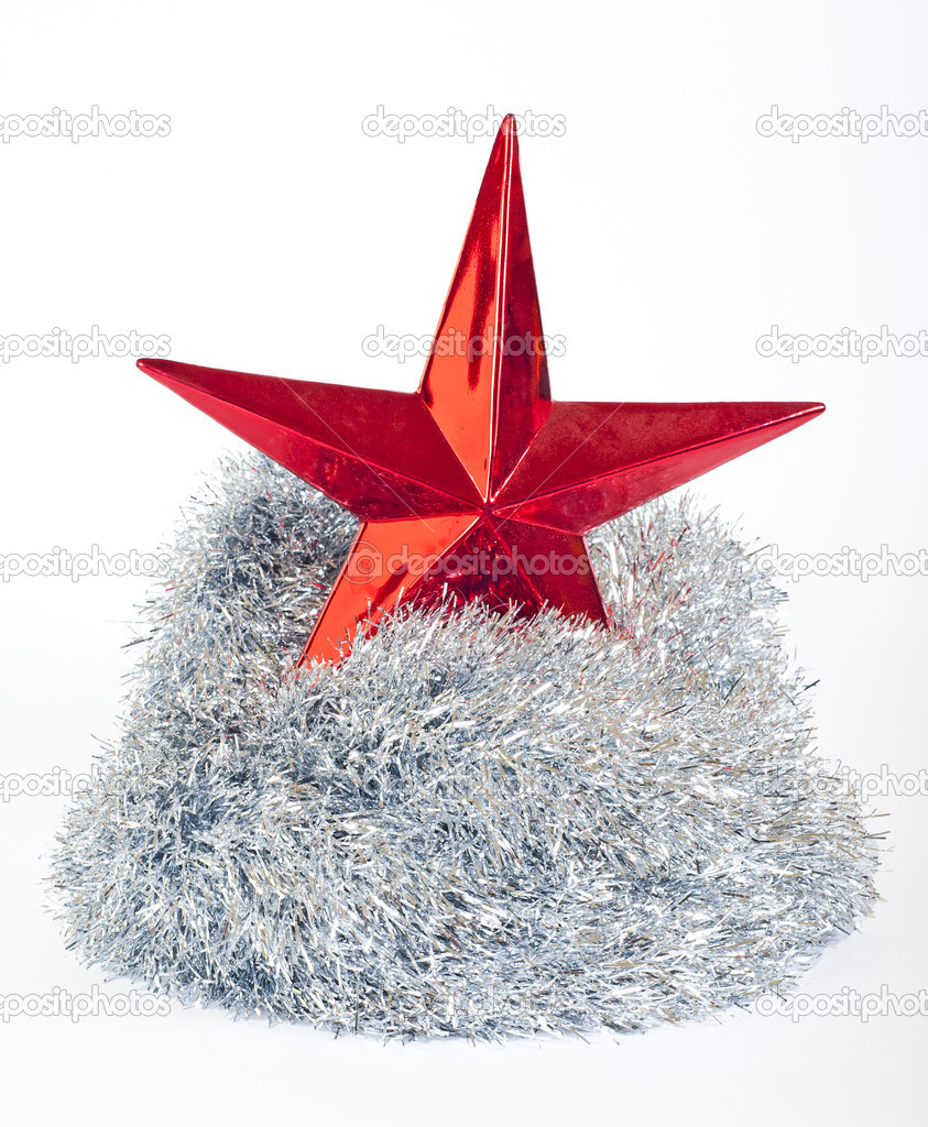 Red christmas star resting on silver tinsel isolated on a white background — Stock Photo #3706172