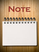 Note Book on wood wall — Stok fotoğraf