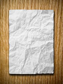 White crumpled paper on red oak wood — Stock Photo