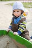 Toddler sitting near sandbox — Stock Photo
