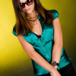 Shy lady in green blouse and sunglasses — Stock Photo