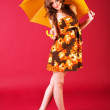 Charming girl sitting in dress with umbrella — Stock Photo