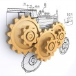 Three golden gears against a background of engineering drawings with shadow — Stock Photo #3497949