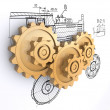 Stock Photo: Three golden gears against a background of engineering drawings with shadow