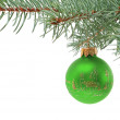 Green christmas ball hanging on a branch of a fur-tree — Stock Photo