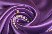 Jewels on purple satin — Stock Photo