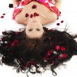 Young girl lies in petals of roses — Stock Photo