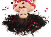 Young girl lies in petals of roses — Zdjęcie stockowe