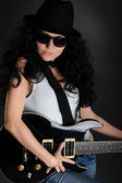 Girl in a hat with a black guitar — Stock Photo