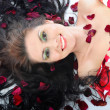 Stock Photo: Lovely young girl in petals of roses