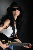Girl in a hat and sunglasses with a guitar in his hands — Stock Photo