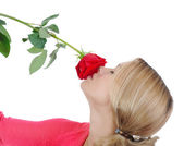 Pretty girl sniffing a red rose. — Stock Photo