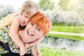 Girl hugs her young mother in the park — Stockfoto
