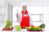Blond girl cuts the tomatoes — Stock Photo