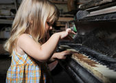 Girl playing on an old piano. — Stock Photo