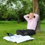 Businessman sitting near a tree — Stock Photo #3637755