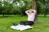 Businessman sitting near a tree — Stock Photo