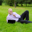 Man with laptop lying on green grass - Stock Photo