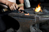 Blacksmith forges iron — Stock Photo