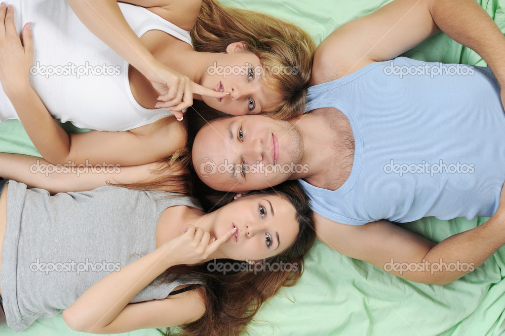 Two beautiful women and man lying on the bed — Stock Photo #3708029