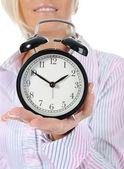 Mujer con un reloj de alarma en una mano. — Foto de Stock