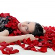 Beautiful brunette in rose petals — Stock Photo #3856525