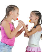 Two smiling girls with candy. — Stock Photo