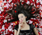 Beautiful brunette in rose petals — Stok fotoğraf