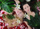 Beautiful women in rose petals — Stock Photo